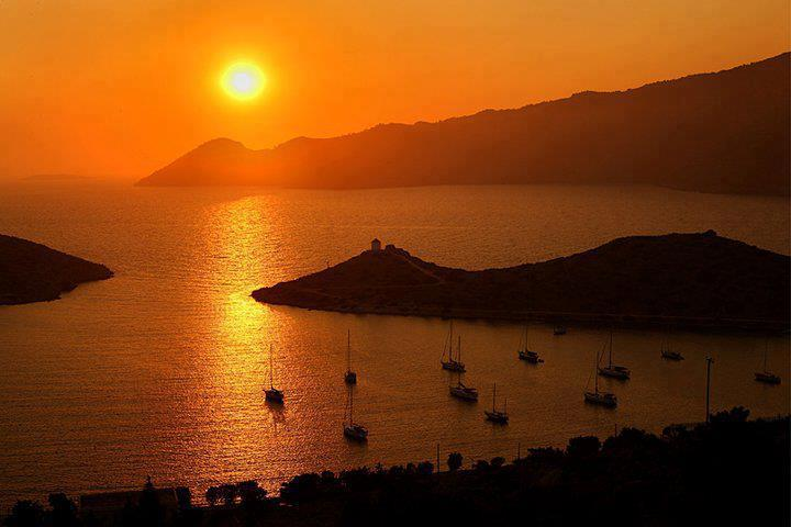 Sunset strikes Symi harbor in Dodecanese Greece